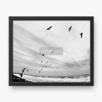 Jesienny krajobraz morski w czerni i bieli. Człowiek spaceruje po piaszczystej plaży w burzliwej pogodzie.