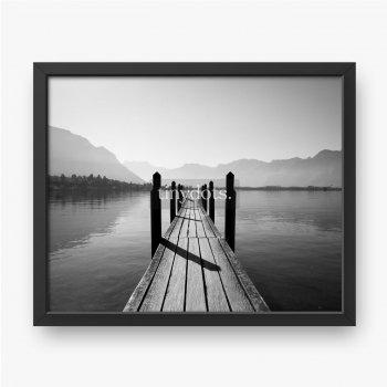 Czarno-biały widok z wąskim drewnianym pomostem na brzegu jeziora