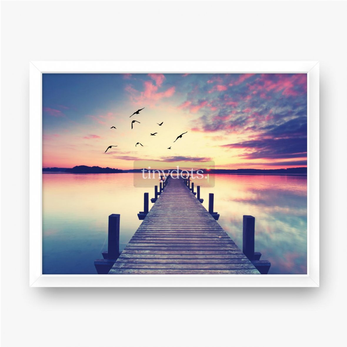 Plakat w ramie Molo na brzegu dużego jeziora z lecącymi ptakami na tle zachodzącego słońca