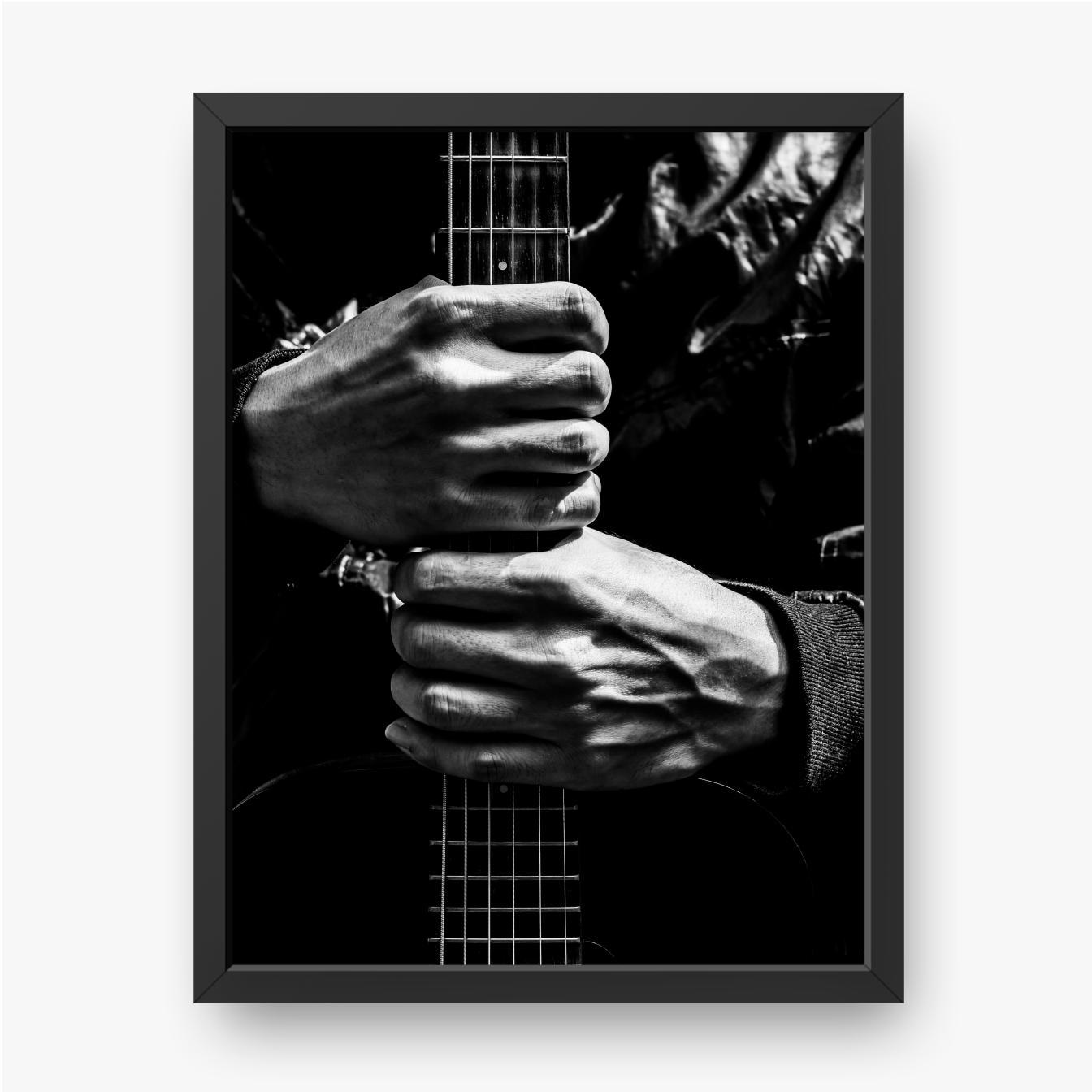 Muzyk trzyma w rękach gitarę