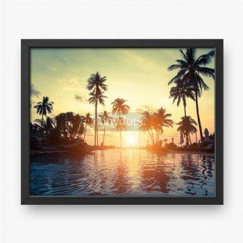 Goldener Sonnenuntergang an der Seeküste mit Palmenreflexion im Wasser